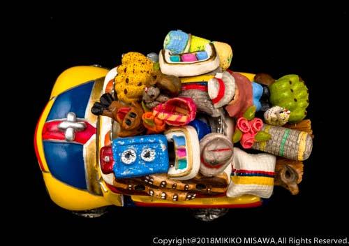 車の置物:車の上には、青いガスコンロ、人形、バナナ、バスケット、帽子、バラの花束、鶏、クッション、マット.....と、所狭しと並ぶ  13341